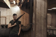 Portrait of man holding a rifle in an indoor shooting range - KKAF02602