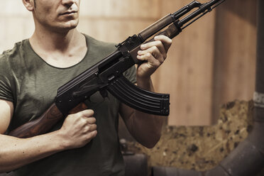 Close-up of man holding a rifle in an indoor shooting range - KKAF02605