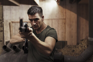 Portrait of man aiming with a rifle in an indoor shooting range - KKAF02608