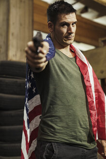 Portrait of man wearing American flag aiming with a gun - KKAF02611
