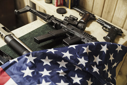Rifles, guns and American flag on table - KKAF02614