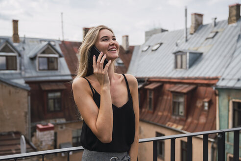 Smiling blond woman on the phone standing on balcony looking up - KKAF02617