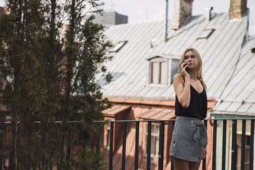 Blond woman on the phone standing on roof terrace - KKAF02620