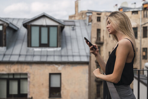 Blond young woman standing on balcony looking at cell phone - KKAF02623