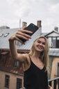 Portrait of smiling blond woman taking selfie on roof terrace - KKAF02626