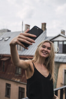 Portrait of smiling blond woman taking selfie on roof terrace - KKAF02626