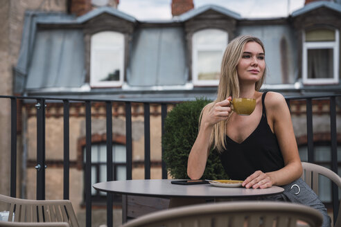 Portrait of blond young woman sitting on roof terrace drinking cup of coffee - KKAF02629