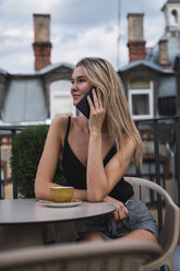 Smiling blond woman on the phone sitting on roof terrace with cup of coffee - KKAF02635