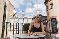 Young woman sitting on balcony with cup of coffee taking notes - KKAF02647