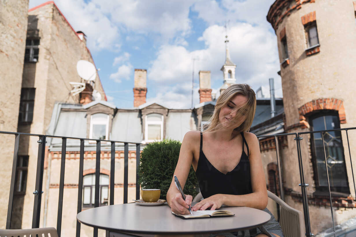 Young woman sitting on balcony with cup of coffee taking notes - KKAF02647 - Kike Arnaiz/Westend61