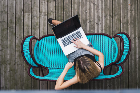 Young woman sitting on turquoise couch on terrace using laptop, top view - KKAF02656
