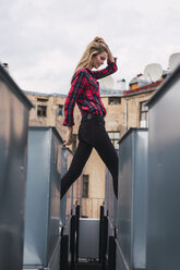Fashionable young woman on rooftop wearing plaid shirt and black jeans - KKAF02659