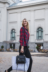 Portrait of smiling young woman with hand bag and shopping bag walking along - KKAF02680