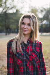 Portrait of blond young woman wearing plaid shirt in autumn - KKAF02683