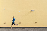 Sportive man running along yellow wall with CCTV camera - KKAF02692