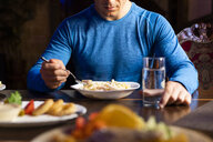 Close-up of athlete eating pasta dish - KKAF02698