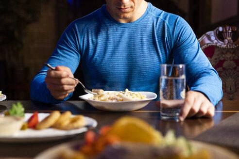 Close-up of athlete eating pasta dish - KKAF02698