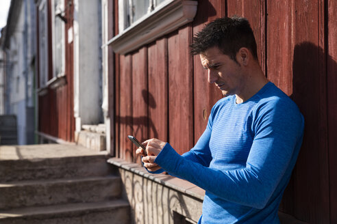 Athlete leaning against house wall using cell phone - KKAF02707