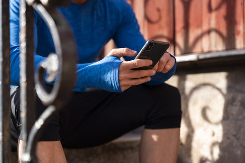 Close-up of athlete sitting on front stoop using cell phone - KKAF02710