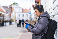 Man with cell phone and headphones in the city - KKAF02716