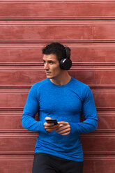 Athlete leaning against house wall holding cell phone - KKAF02719