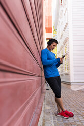 Athlete leaning against house wall with cell phone and headphones - KKAF02722