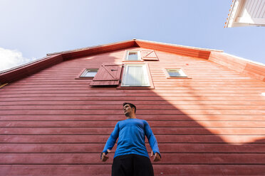 Low angle view of athlete standing in front of red house - KKAF02725