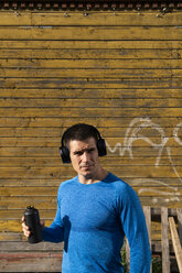 Athlete in front of wooden house with headphones and drinking bottle - KKAF02731