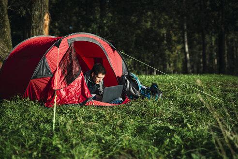 Man camping in Estonia, sitting in his tent, using laptop - KKA02758
