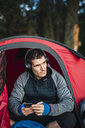 Man camping in Estonia, sitting in his tent, lietsning music from his smartphone - KKA02761