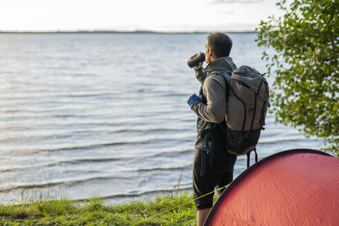 Man camping in Estonia, standing at lake with a backpack, drinking coffee - KKA02770