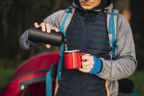 Man camping in Estonia, pouring water in a cup - KKA02773