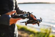 Man holding drone and telecontrol at a lake - KKA02776