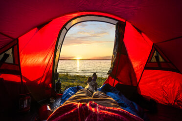 Man camping in Estonia, watching sunset lying in tent - KKA02779