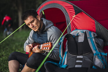 Man camping in Estonia, sitting in his tent, playing the ukulele - KKA02782