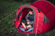 Man camping in Estonia, sitting in tent, using laptop - KKA02788