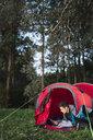 Man camping in Estonia, sitting in his tent, using smartphone - KKA02791
