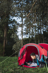 Man camping in Estonia, sitting in his tent, using smartphone - KKA02791