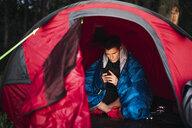 Man camping in Estonia, sitting in his tent, using smartphone - KKA02794