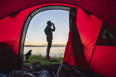 Man camping in Estonia, standing in front of tent, watching sunset - KKA02797