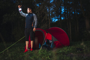 Man camping in Estonia, standiing in front of tent holding lantern - KKA02800