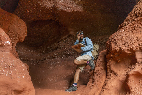 Young man sitting in a cave, looking through binoculars, holding map - AFVF01862