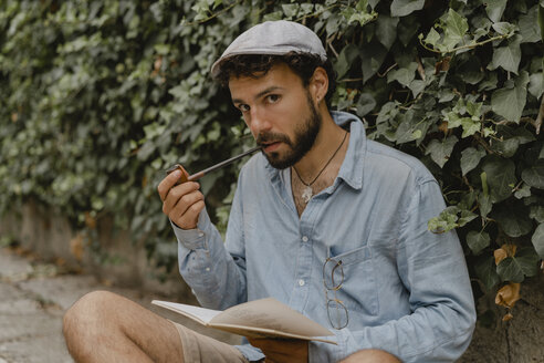 Young man smoking pipe, reading a book - AFVF01880