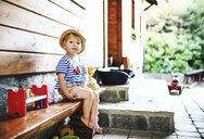 Portrait of toddler sitting on bench in front of house - HAPF02797