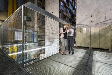 Women using laptop in high rack warehouse - DIGF05422