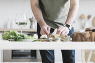Man preparing salad at home, partial view - KMKF00597