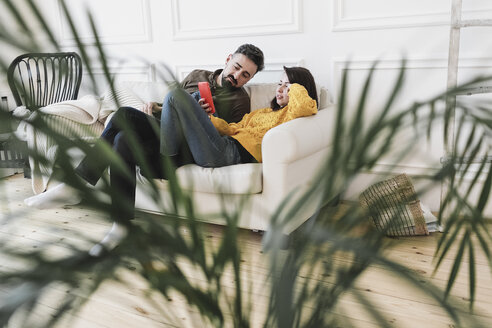 Couple sitting on the couch in the living room of new home looking at cell phone - KMKF00603