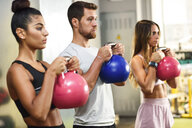 Young people doing kettle ball workout in a gym - JSMF00483