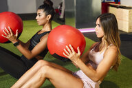 Young people doing ab training with fitness balls - JSMF00486
