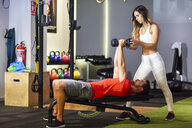 Personal trainer assisting client with weight training, lifting dumbells, lying on bench - JSMF00492